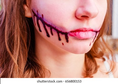 Halloween Chelsea Smile make up on  woman's face.  Halloween Sliced Mouth, make-up. Girl with cutted mouth, Halloween make up