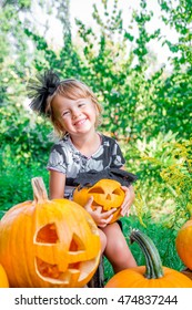 Halloween. Child dressed in black with jack-o-lantern in hand, trick or treat. Happy little girl with pumpkin in the wood, outdoors.