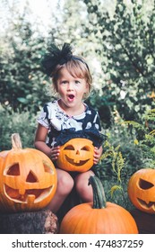 Halloween. Child dressed in black with jack-o-lantern in hand, trick or treat. Little girl with pumpkin in the wood, outdoors. Wow. Toned photo.