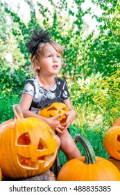 Halloween. Child dressed in black with jack-o-lantern in hand, trick or treat. Little girl with pumpkin in the wood, outdoors.