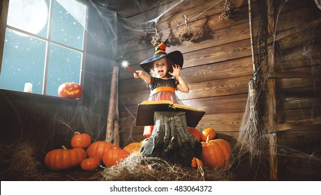 Halloween. child little witch with magic wand and reading a magical book of spells in the old hut