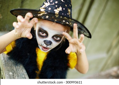 Halloween child with painted face and frightening expression