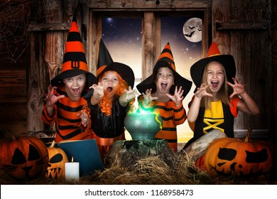 Halloween.The children of witches and wizards cooking potion in the cauldron with pumpkin and spell book.