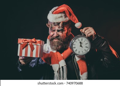 0d98ca0a8a950 Halloween or christmas man devil in santa hat. Hipster with satan horns  hold present box