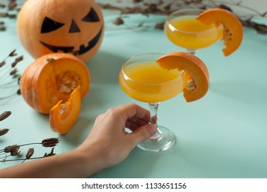 Halloween cocktail, pumpkin orange drink with spices. DFestive decoration with dry flowers and pumpkins guards.
