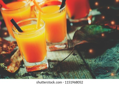 Halloween cocktail, pumpkin orange drink with spices. Dark vintage dirty background. Festive decoration with candles and pumpkins guards. Selective focus  and toned image