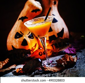 Halloween cocktail, pumpkin orange drink with spices. Dark vintage dirty background. Festive decoration with candles and pumpkins guards. Selective focus