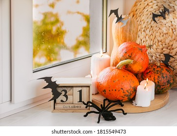 Halloween composition of pumpkins, candles, paper cut bats, party flags, paper fans on a wooden tray on a windowsill. An example of home decor for Halloween. Autumn mood. Copy space, horizontal