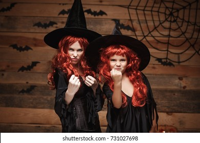 Halloween Concept - Beautiful caucasian mother and her daughter with long red hair in witch costumes witch cheeful fighting facial expression.