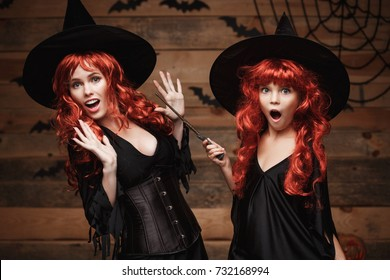 Halloween Concept - Beautiful caucasian mother and her daughter with long red hair in witch costumes and magic wand celebrating Halloween posing