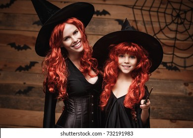 Halloween Concept - Beautiful caucasian mother and her daughter with long red hair in witch costumes and magic wand celebrating Halloween posing with over bats and spider web on Wooden background.