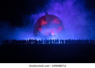 Halloween concept. Blurred silhouette of giant Jack-o-lantern pumpkin with scary smiling face behind crowd at night. People looks at a big pumpkin at night. Selective focus.