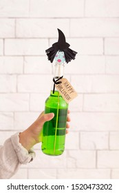 Halloween concept. Green party drink with paper witches head over bricks wall background, vertical panorama