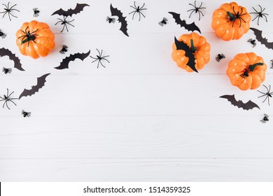 Halloween concept. Pumpkins, spiders and bats on white wooden background. Flat lay, top view, copy space