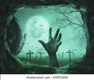 Halloween concept: Scary hand in cave stone on on death tree with creepy cemetery background.