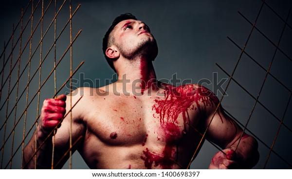 Halloween concept. Scary monster just murdered his victim. Strong aggressive monster behind grid. Prison for monster. Psycho mad man. Murderer mythical creature. Muscular man nude torso soiled blood.