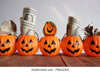 Halloween concept, smile face pumpkins with dollar money, doll and crumpled paper on old vintage wood in white background