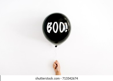 Halloween concept. Word Boo on black balloon in girl's hand. Flat lay, top view.