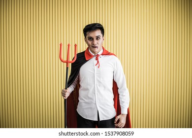 Halloween concept of young Asian man in costume dracula and hold spear on yellow background. Portrait of teen man dressed up as dracula for celebrate Halloween festival.
