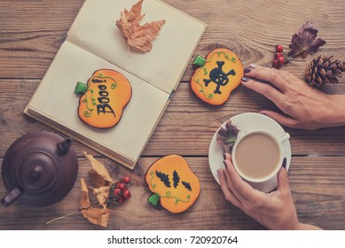 Halloween cookies on the table. Women's hands, a cup of coffee, a book and glasses, Halloween postcard, toned image