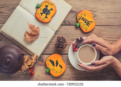 Halloween cookies on the table. Women's hands, a cup of coffee, a book and glasses