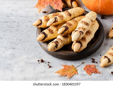 Halloween cookies, witches fingers cookies with almond nuts nails and chocolate, autumn funny buiscuits, seasonal festive sweets. Halloween party concept. Copy space, close up view,concrete background