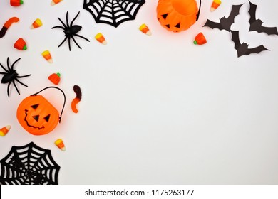 Halloween corner border of scattered candy and decor. Flat lay over a white background. Copy space.