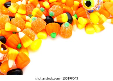 Halloween corner border of varied candies over white