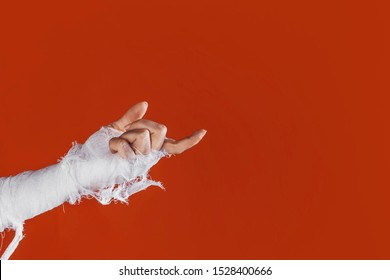 Halloween, costume image. The mummy's hand in bandages making gestures. Come to me, the mummy's hand beckons with its finger, copy space. on a bright orange background