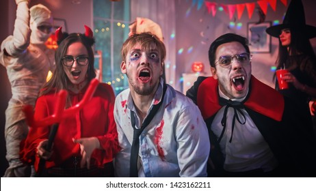 Halloween Costume Party: Brain Dead Zombie, Blood Thirsty Dracula, Bandaged Mummy Beautiful Witch and Seductive She Devil are Posing and Making Scary Faces