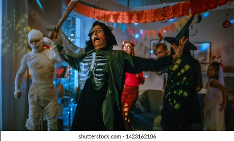 Halloween Costume Party: Group of Monsters Dancing in Decorated Room with Disco Lights. Terrifying Screaming Death Poses on Foreground. Dead Zombie, Vampire Dracula, Mummy, Beautiful Witch and Devil