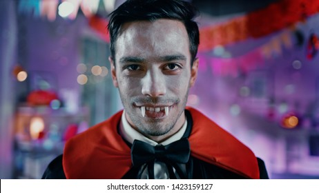 Halloween Costume Party: Portrait of Count Dracula Smiling Creepily, Shows His Deadly Bloody Fangs, Exercises His Deadly Bite. In the Background Thematically Decorated Neon Colorful Room