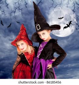 halloween costumes kid girls on moon night sky with bats [Photo Illustration]