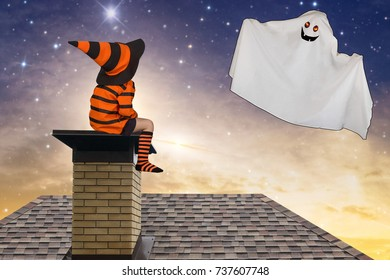 Halloween.Boy in Halloween costumes sitting on the roof and looks up at the flying Ghost.