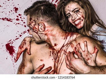 Halloween couple of handsome man and sexy pretty girl with long hair and red blood as traditional autumn holiday symbol. Sexy woman vampire bites a man's neck