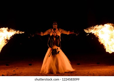 Halloween couple standing with flamethrower. a big fire
