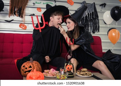 Halloween. couple young caucasian man and woman in vampires and witch clothing feeding sweet snack together and sitting on sofa in halloween party at home, love, holiday and halloween festival concept