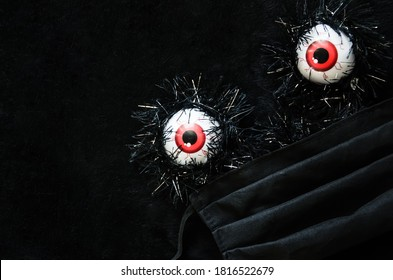 Halloween covid-19 concept. Halloween decor eyeballs in medical protective mask with copy space. Halloween 2020 during the coronavirus pandemic.
