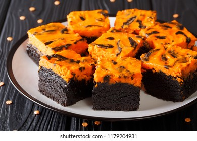 Halloween Cream Cheese Brownies cake delicious dessert for a festive treat closeup on a plate on a table. horizontal