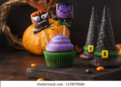 Halloween cupcake decorated with cake pops or chocolate dipped marshmallow with funny monster faces and wafer witch hats. Selective focus.