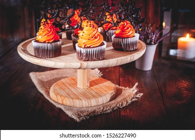 Halloween cupcakes with buttercream and chocolate spiderwebs on dark, rustic, wooden background
