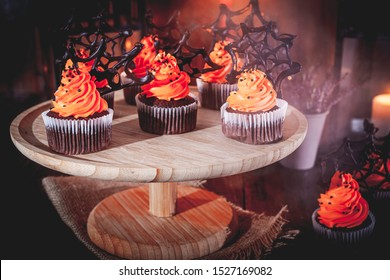 Halloween cupcakes with buttercream and chocolate spiderwebs in the mist. Dark, rustic, wooden background