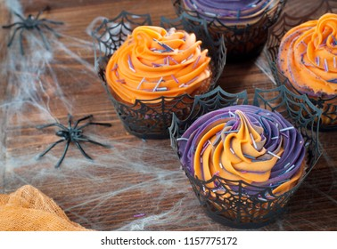 Halloween cupcakes decorated with whipped cream and sprinkles on rustic wooden table covered with web and spiders; selective focus.
