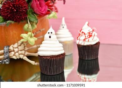 Halloween cupcakes. Spooky ghost bloody cupcakes. Halloween treats on pink wood background. Halloween treats on wooden pink background with palm of skeleton. Halloween pumpkin decorated with flowers.