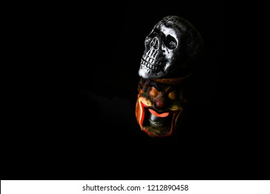 Halloween dark scary horror story ideas concept with jocker candle light and silver skull human isolated on black background