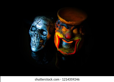 Halloween dark scary horror story ideas concept with joker candle light pot and silver skull human isolated on black background
