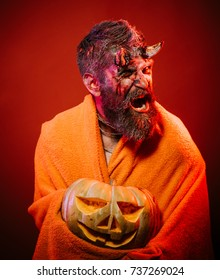 Halloween darkness and light concept. Man devil hold pumpkin on red background. Demon scream in blanket with jack o lantern. Satan with bloody horns, beard, blood, wounds. Trick or treat.