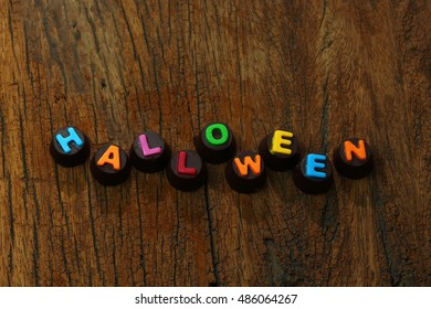 Halloween Day : colourful letter chocolate on wood background. Free space for text and selective focus.