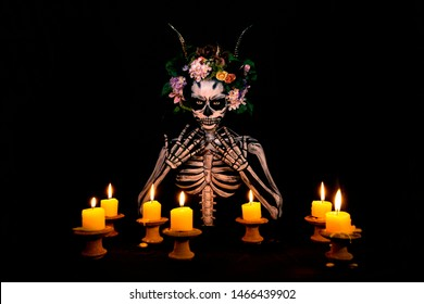 Halloween, Day of the dead bodypaint portrait decorated by flowers on head and candle lights on the tabel in the dark room.