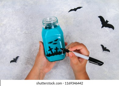 Halloween decor. Handicraft from a jar. Bats on a light table. The concept for Halloween. DIY.